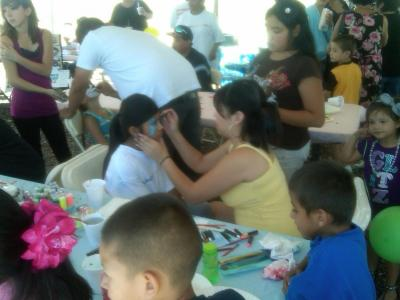 Medium shot of kids getting their faces painted at a community event