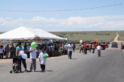 A wide shot of a community event with people and a large tent in the background