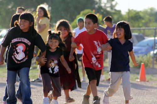 Group of children holding hands and running
