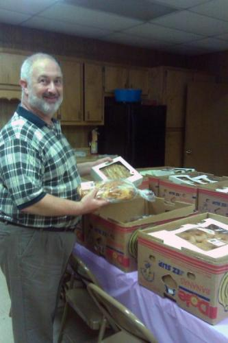 Man organizing donated food into boxes